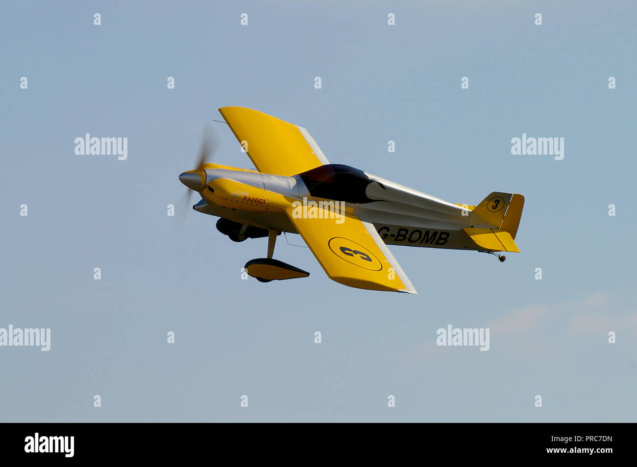 Ford Cassutt Racer IIIM G-BOMB racing plane displayed by Richard Grace as part of the Dukes of Cassutt display team flying in blue sky - Stock Image