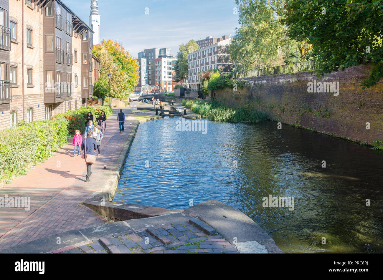 People walking along the canal towpath at Cambrian Wharf, Birmingham in autumn sunshine - Stock Image