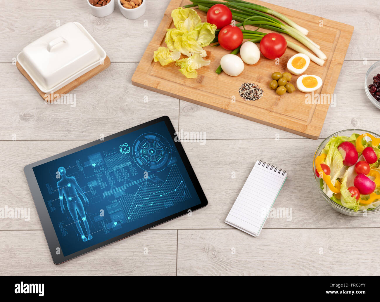 Healthy food composition with tablet. Body diagnosis on the screen - Stock Image