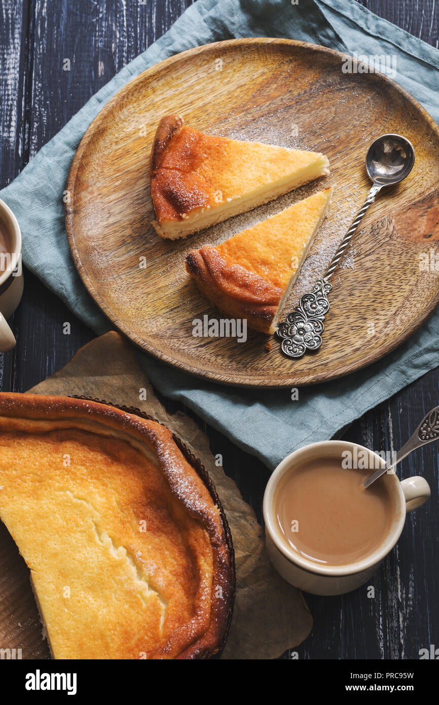 Cheesecake slices on a wooden plate and coffee with milk - Stock Image