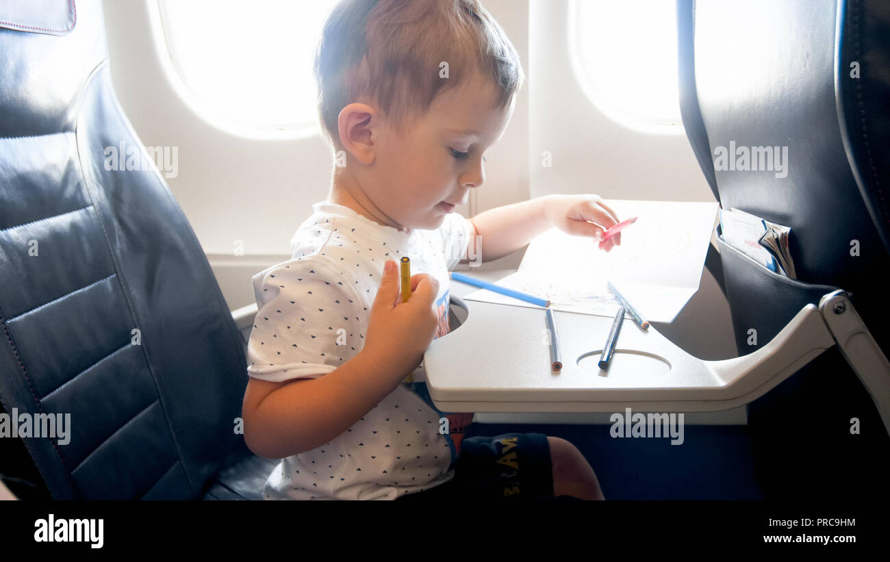 Concentrated toddler boy drawing in copybook with pencils during flight in airplane