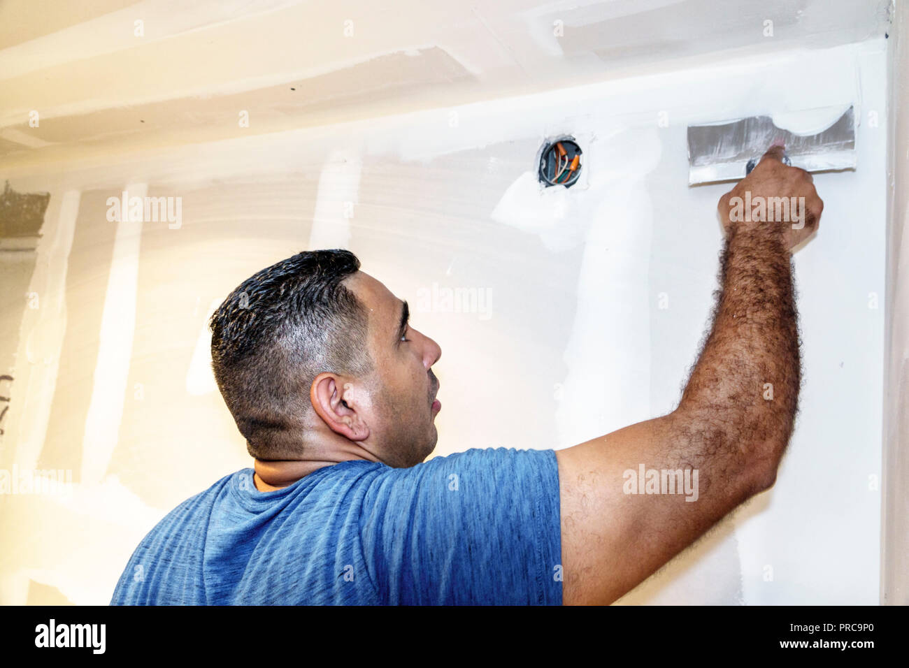 Miami Beach Florida contractor renovation repair drywall Hispanic man working spreading plaster compound putty scraper knife - Stock Image