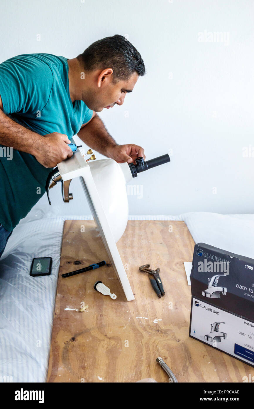 Miami Beach Florida contractor installing bathroom sink Hispanic man working faucet - Stock Image