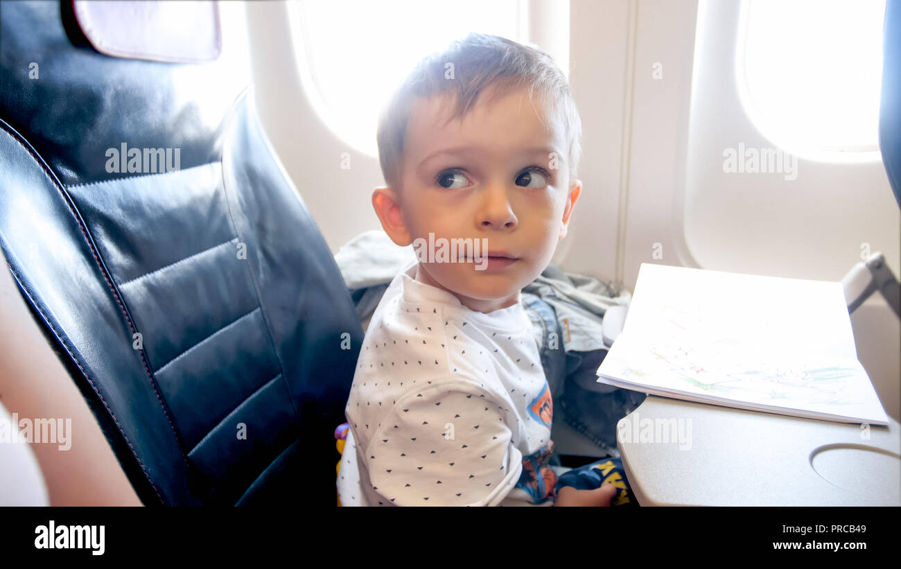 Portrait Of 2 Years Old Toddler Boy Flying In Airplane