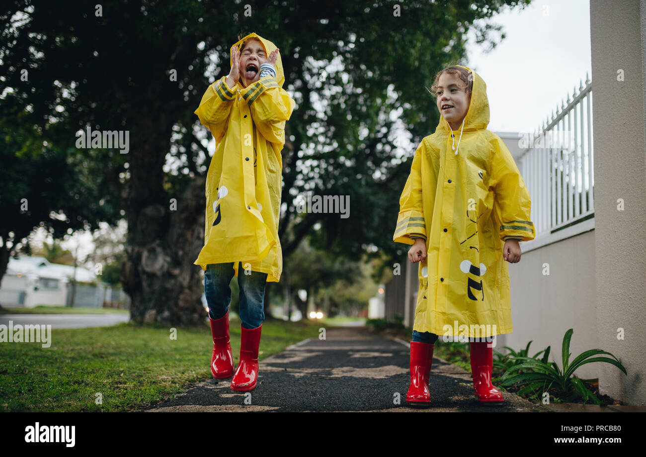 27106166765b Two little children outdoors on rainy day. Twin sisters having fun outdoors  wearing waterproof clothes and rain boots.