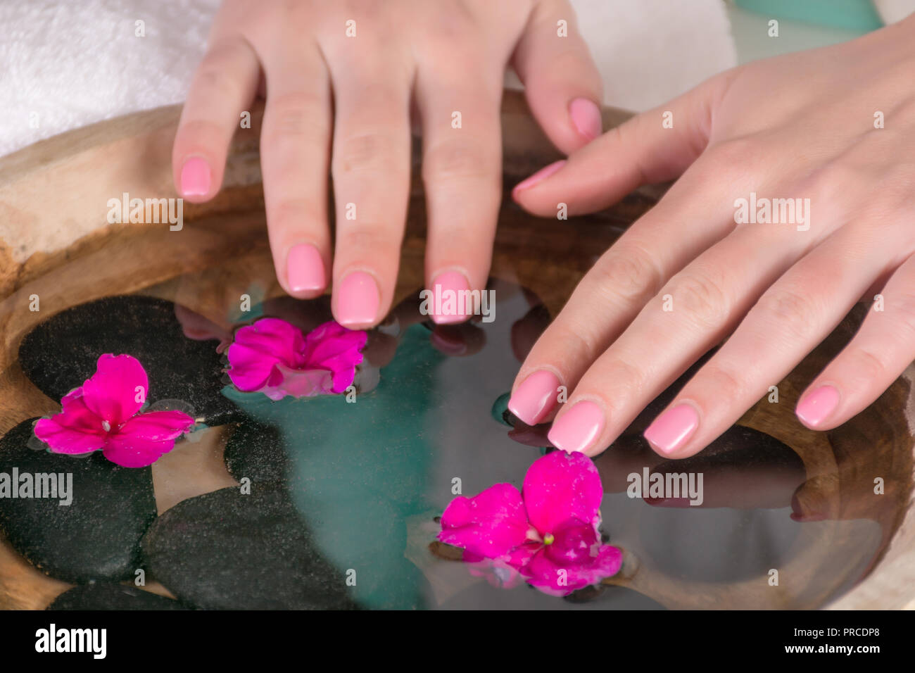 Woman Hands With Gently Pink Nails Gel Polish Above Water With