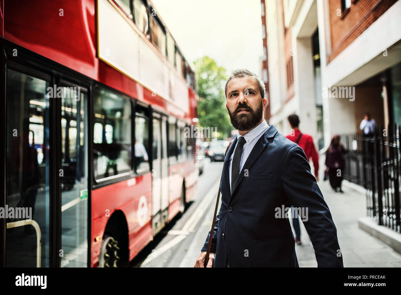 Hipster businessman standing on the street, waiting for the bus in London. - Stock Image