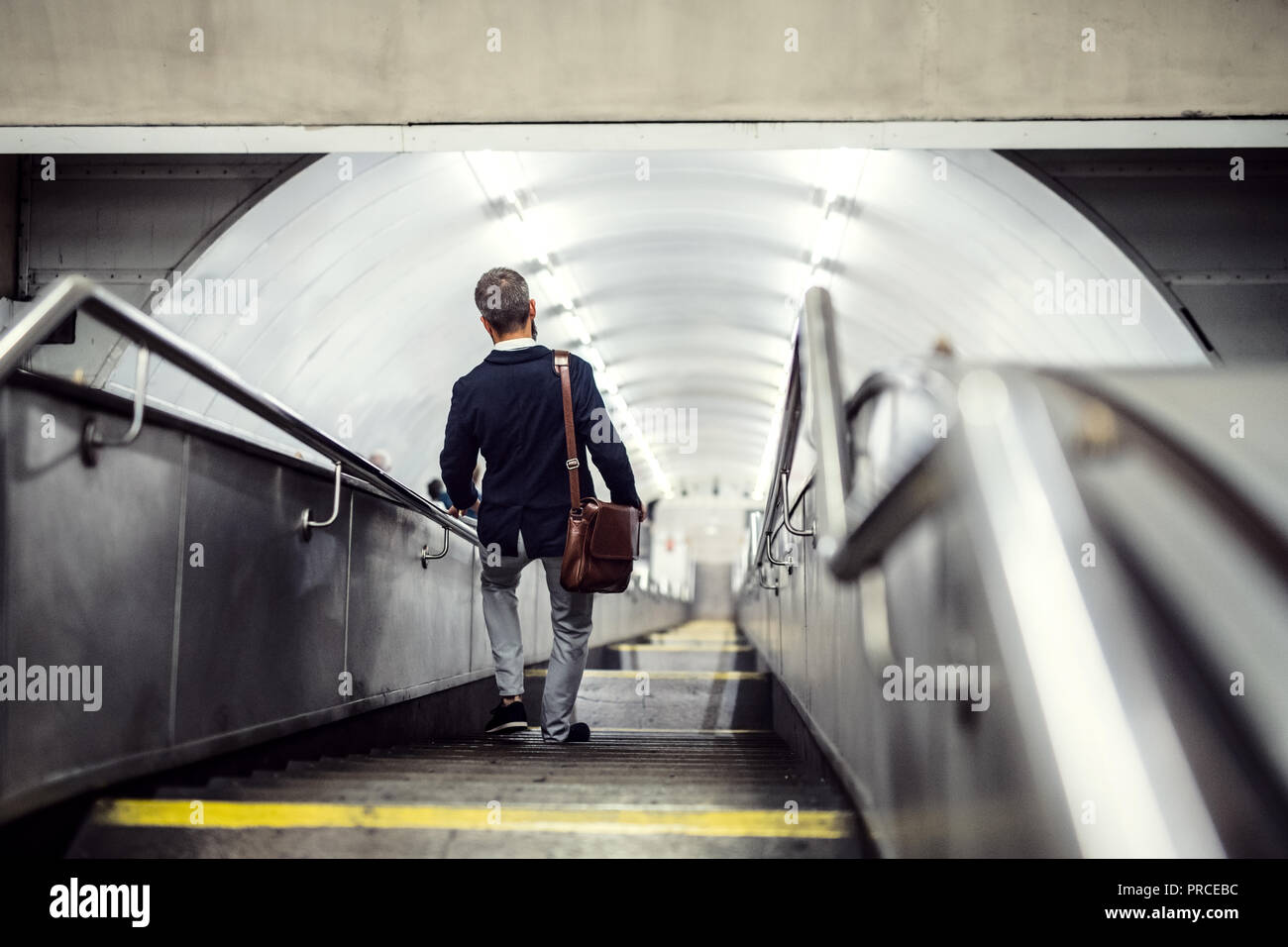 Rear view of hipster businessman walking down the stairs in subway, travelling to work. - Stock Image