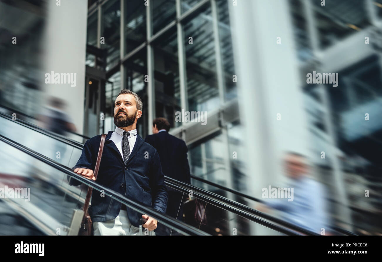 Hipster businessman using escalator in city, travelling to work. - Stock Image