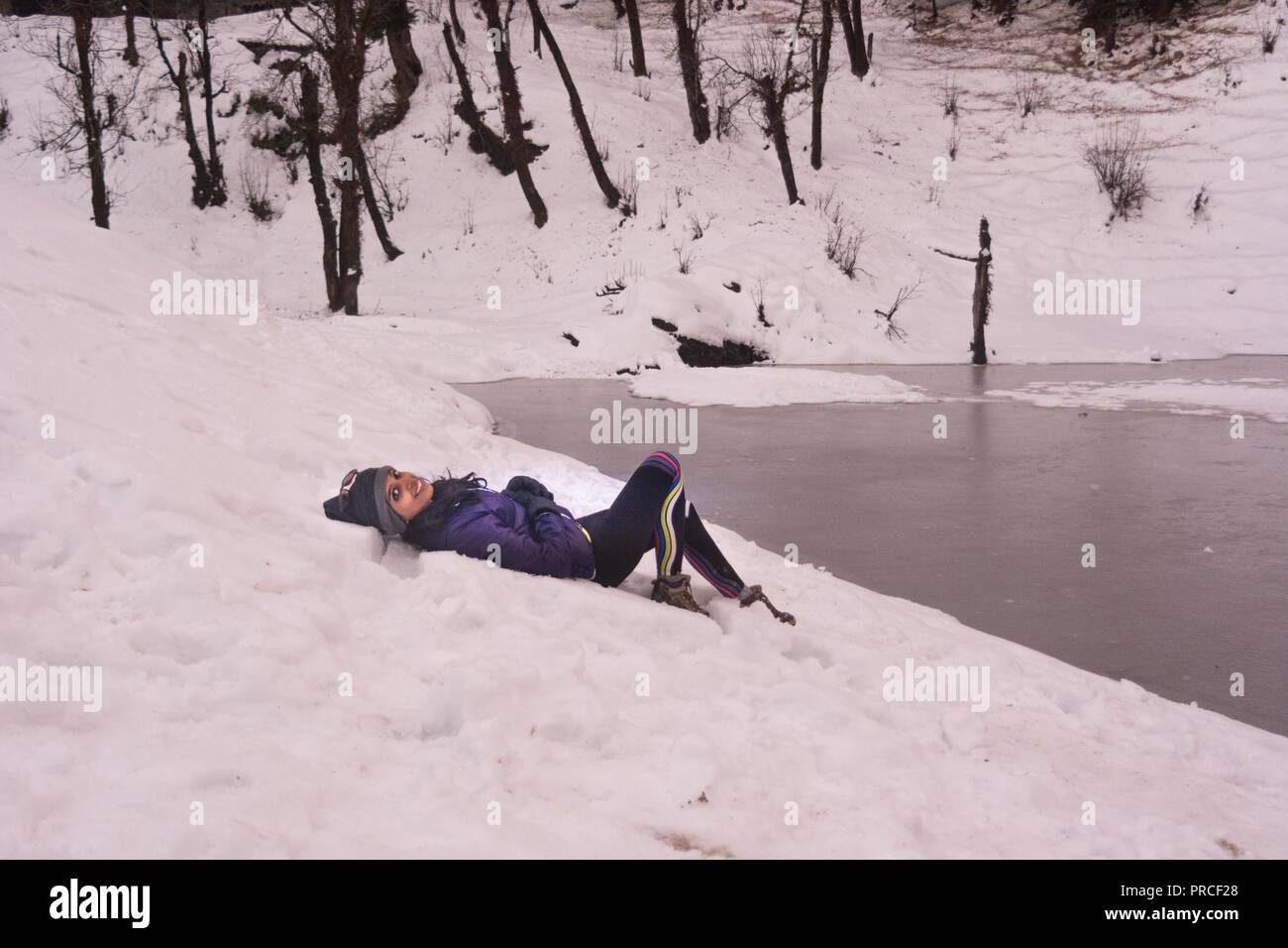 A girl lying down on snow by the lake at Kedarkantha trek - Stock Image