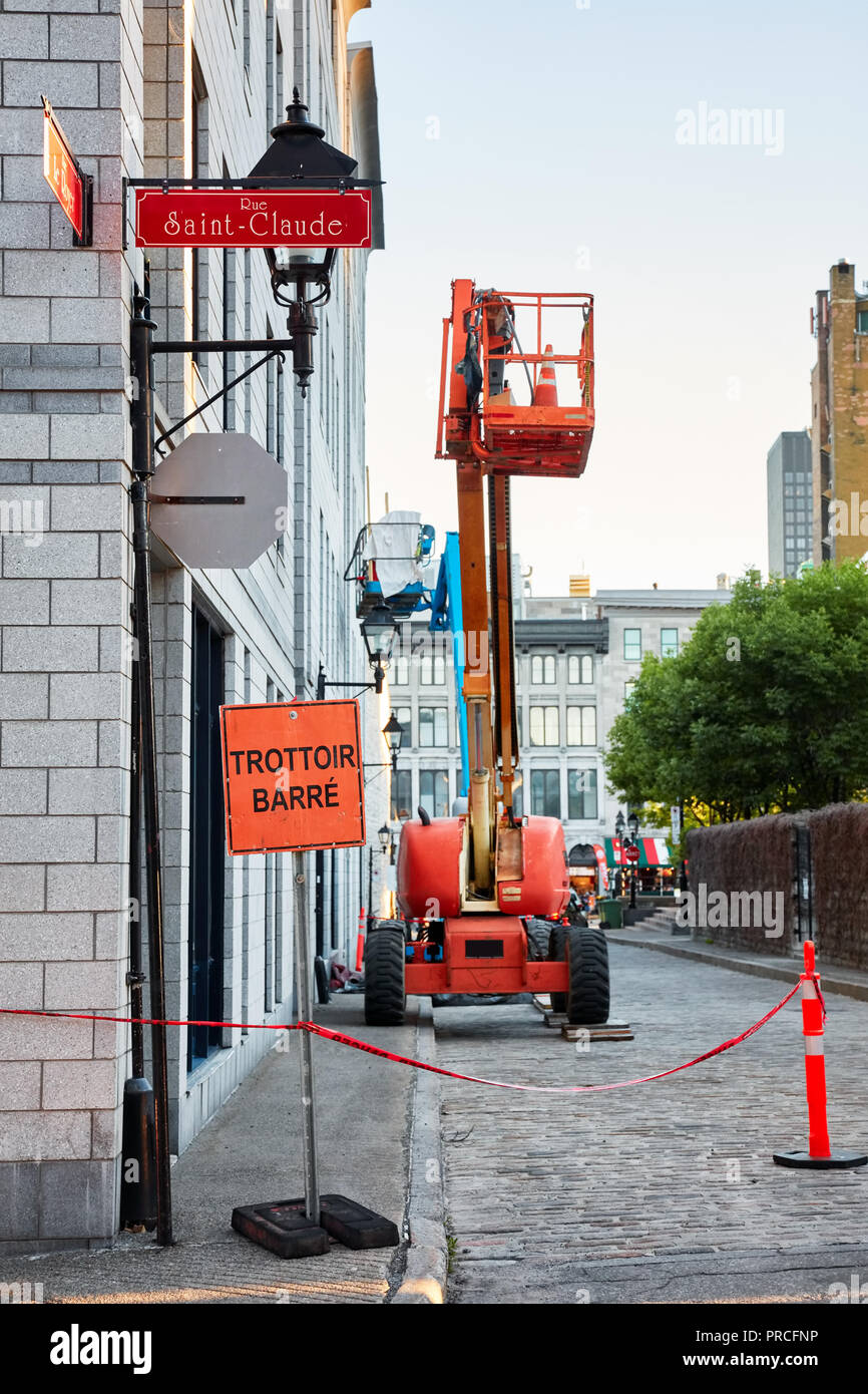 Work lift truck executes construction maintenance on Rue le Royer street and pavement closed (trottoir barre) sign in Montreal, Quebec, Canada - Stock Image