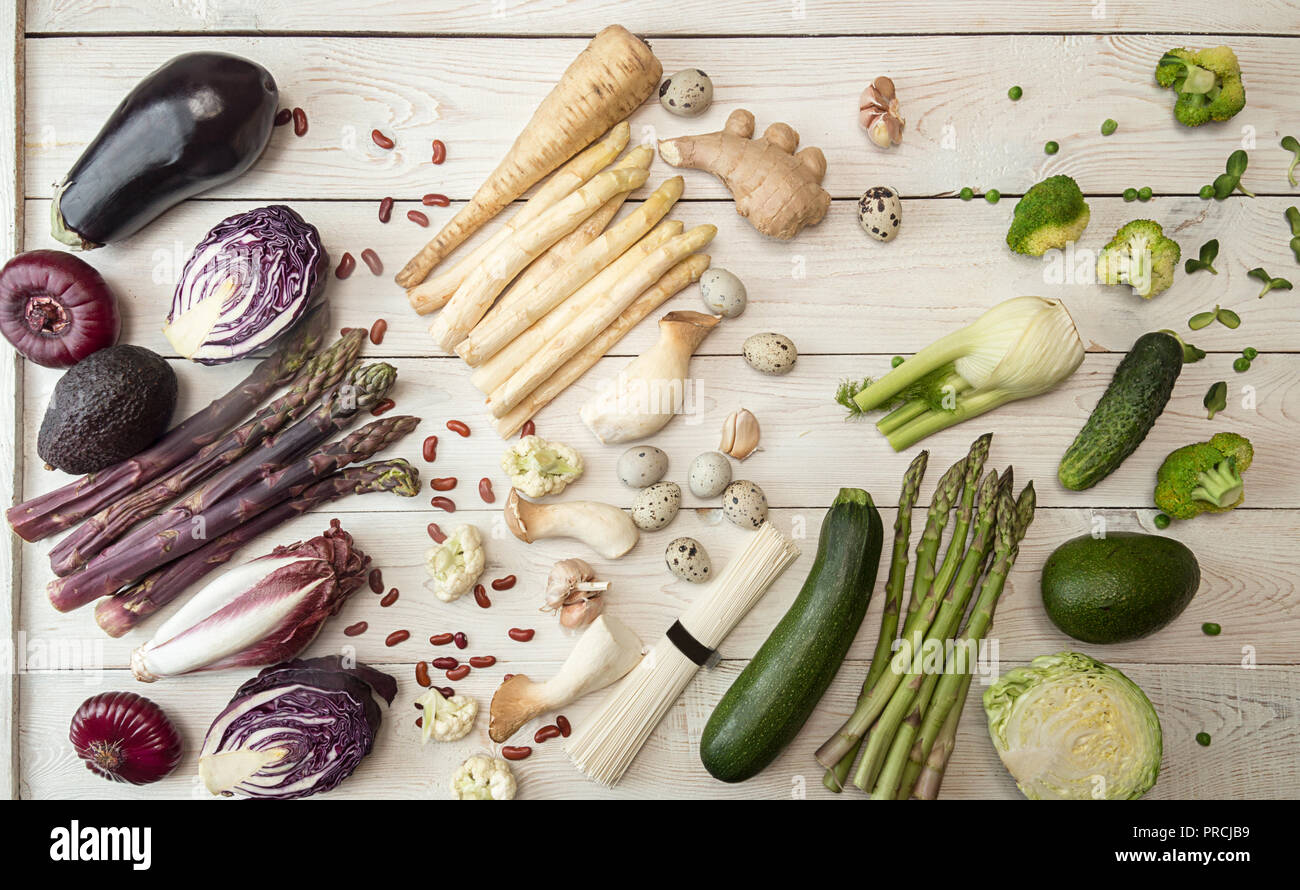 Plant based modern flat lay big set collection rows of white red purple green vegetables on white background. Asparagus, red cabbage, avocado, eggplan Stock Photo