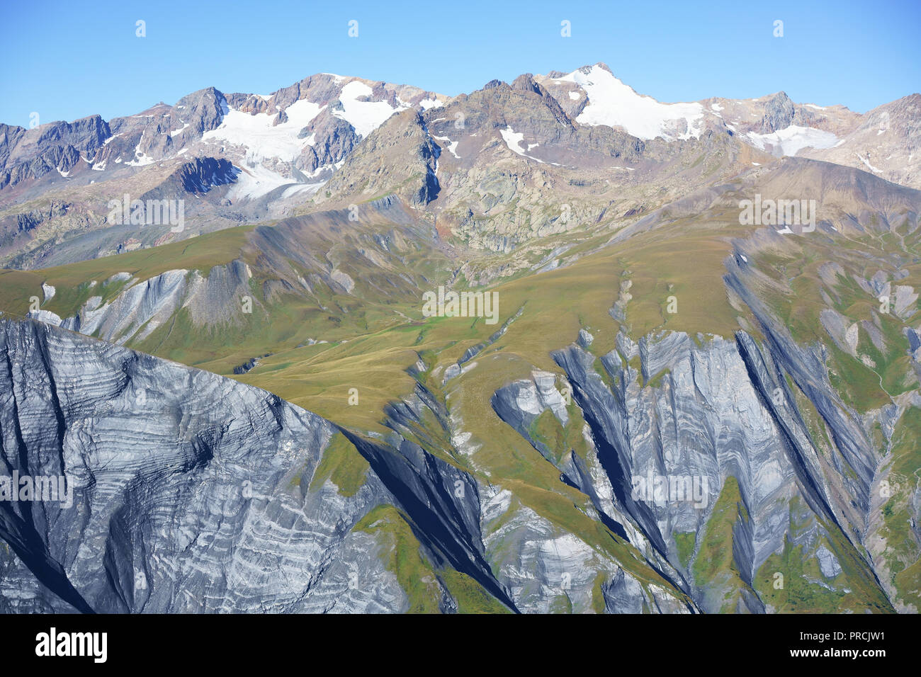 LES GRANDES ROUSSES MASSIF WHICH RISES TO 3465 METERS AT PIC BAYLE (aerial view from the east). Auvergne-Rhone-Alpes, France. - Stock Image