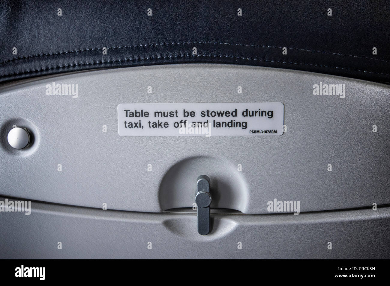 Airplane passenger table usage sign indicating table use during landing and takeoff. - Stock Image