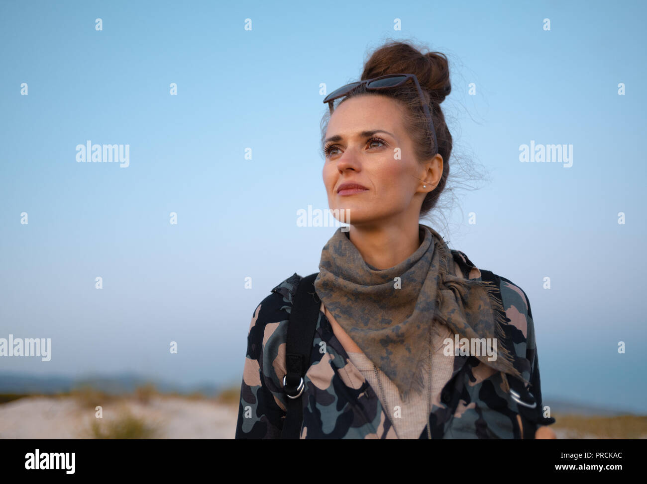 pensive traveller woman looking into the distance against blue sky - Stock Image