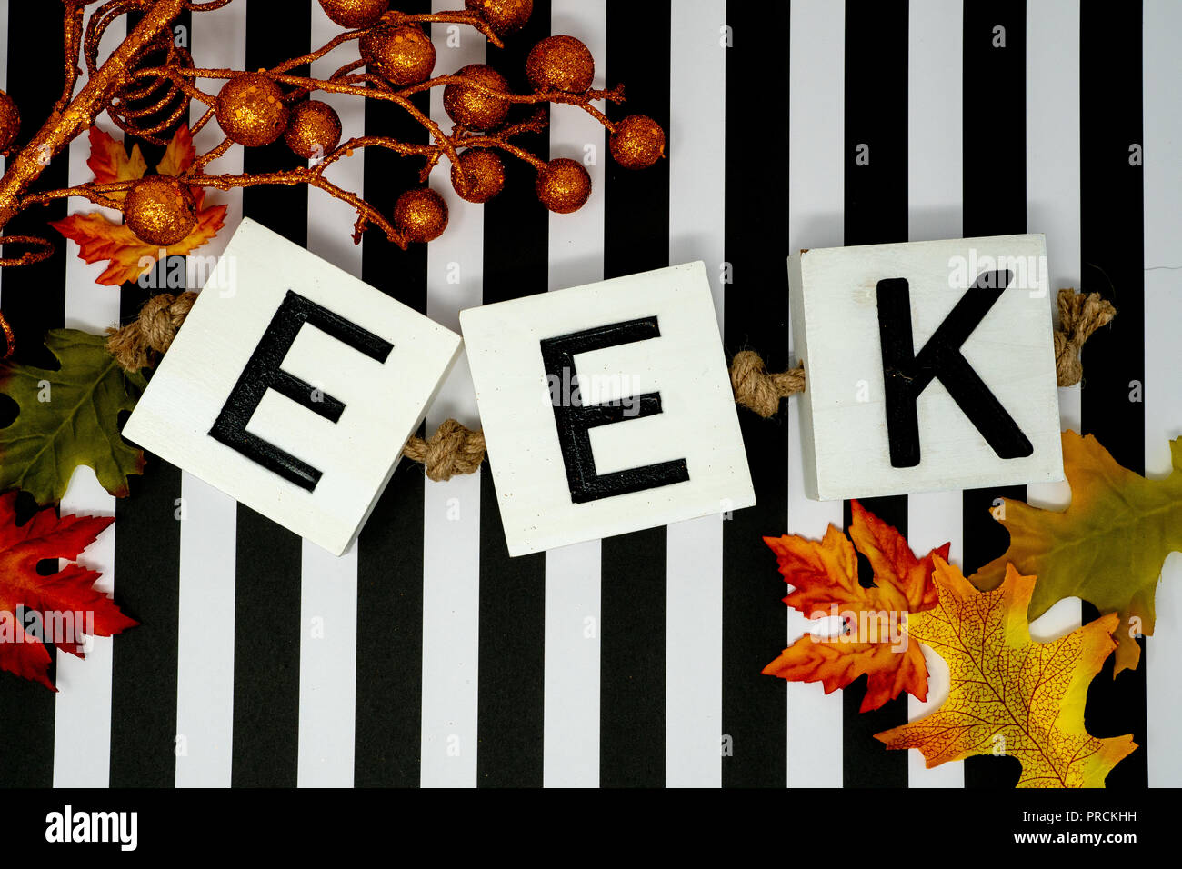 Eek Halloween phrase letters on fun black and white stripe background.  Maple leaves and orange glittery stems for festivity. Useful for Halloween pro - Stock Image