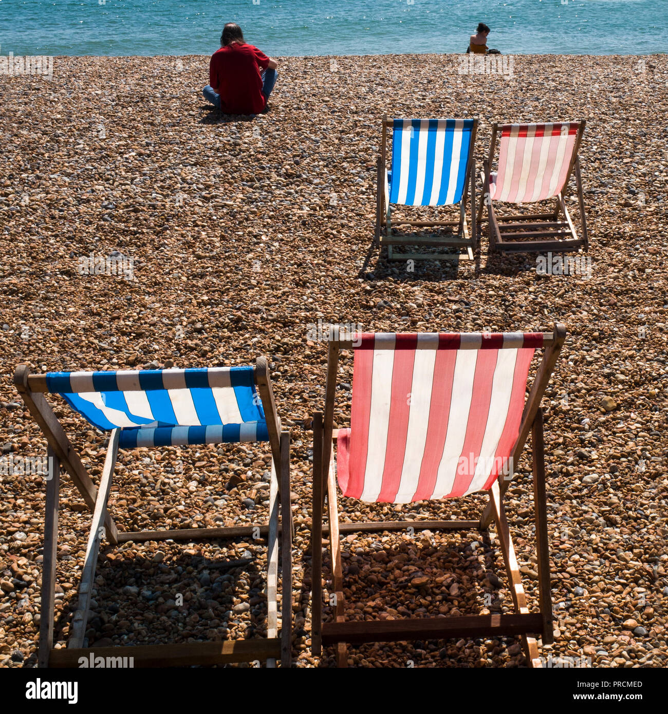 Empty deck chairs on Brighton beach with burnt out ruins of West pier and sea shore in background Stock Photo