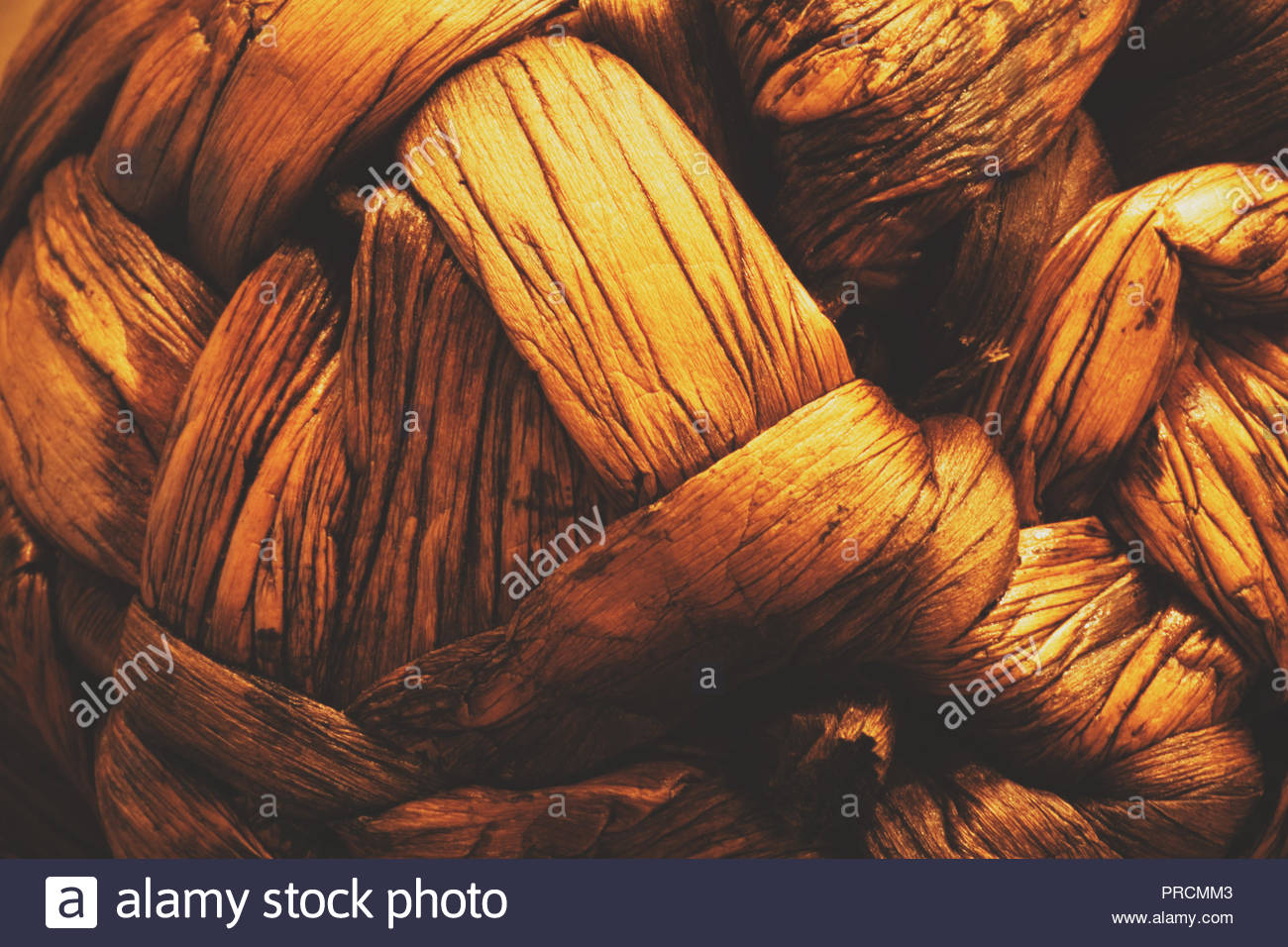 Ball of woven, dried and stained banana leaf closeup as abstract background. - Stock Image
