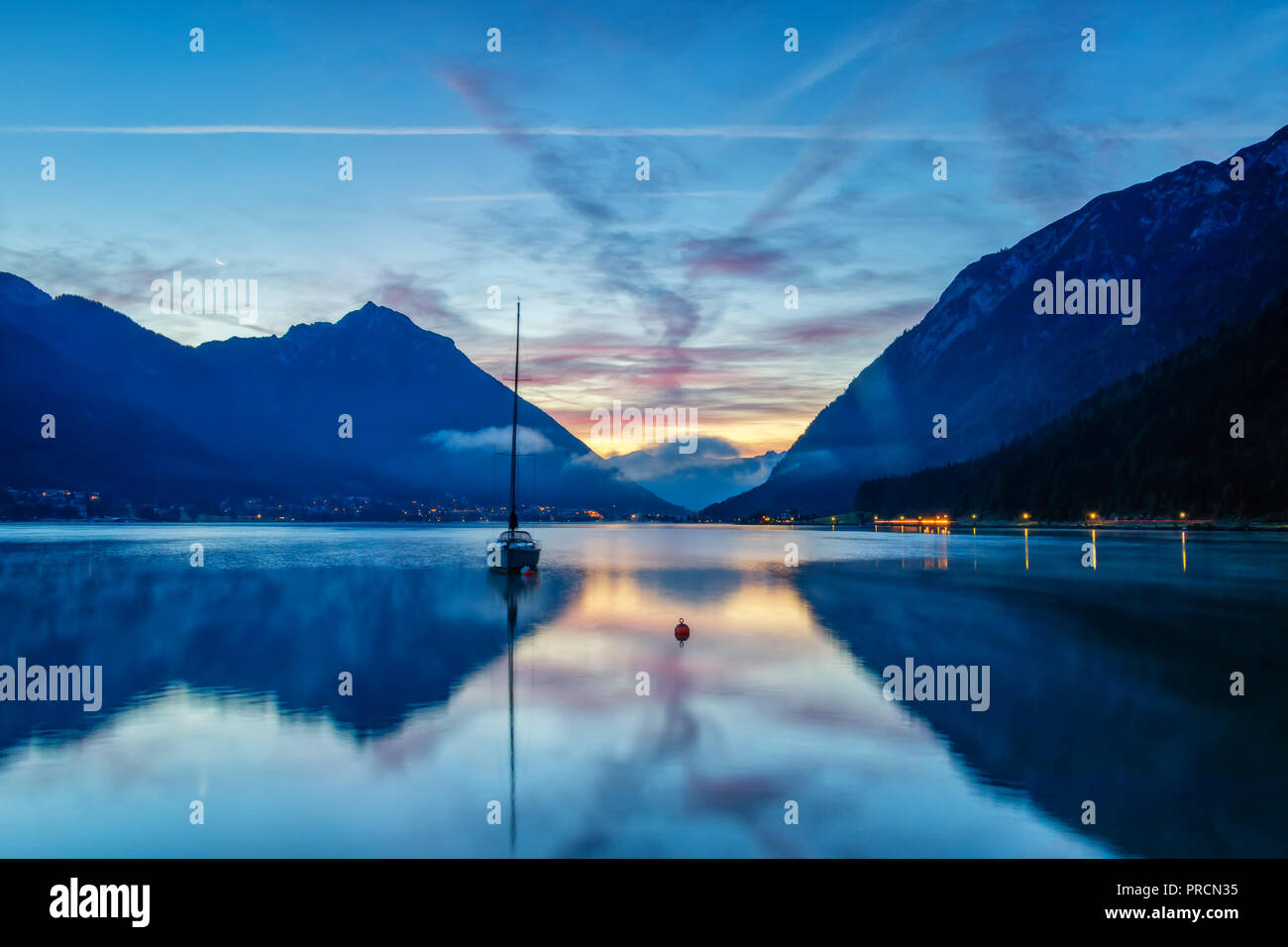 A sailboat in front of a colorful sunrise at the Lake Achensee in Austria. - Stock Image