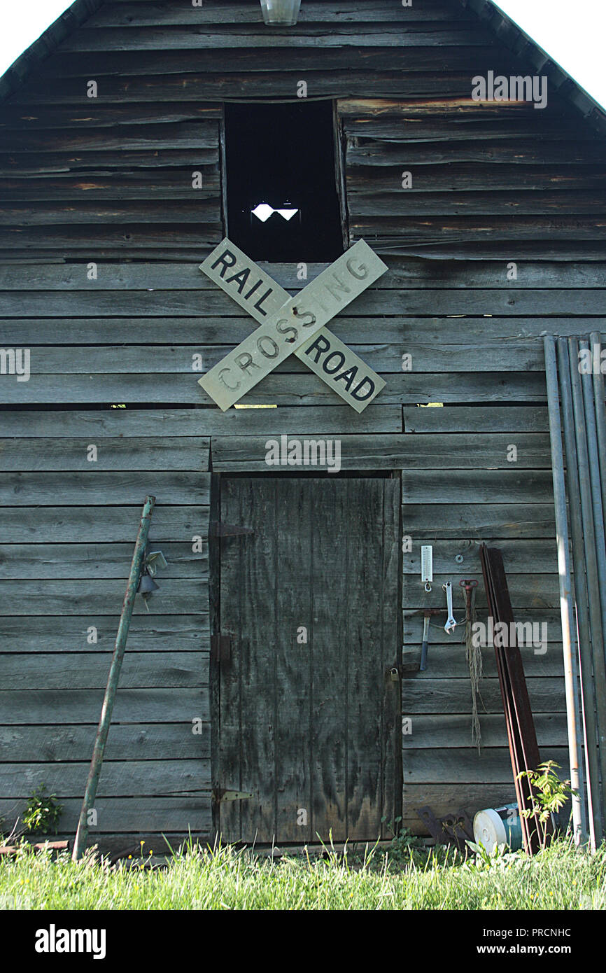Railroad crossing sign used as decoration on old wooden barn