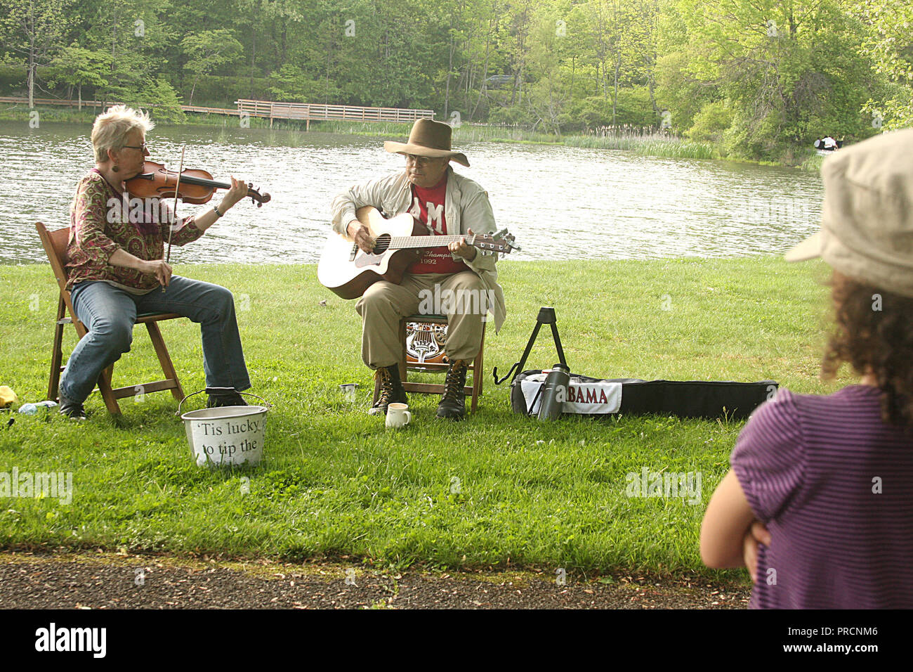 Woman with violin and man with guitar performing outdoors by Abbott Lake on Virginia's Blue Ridge Parkway Stock Photo