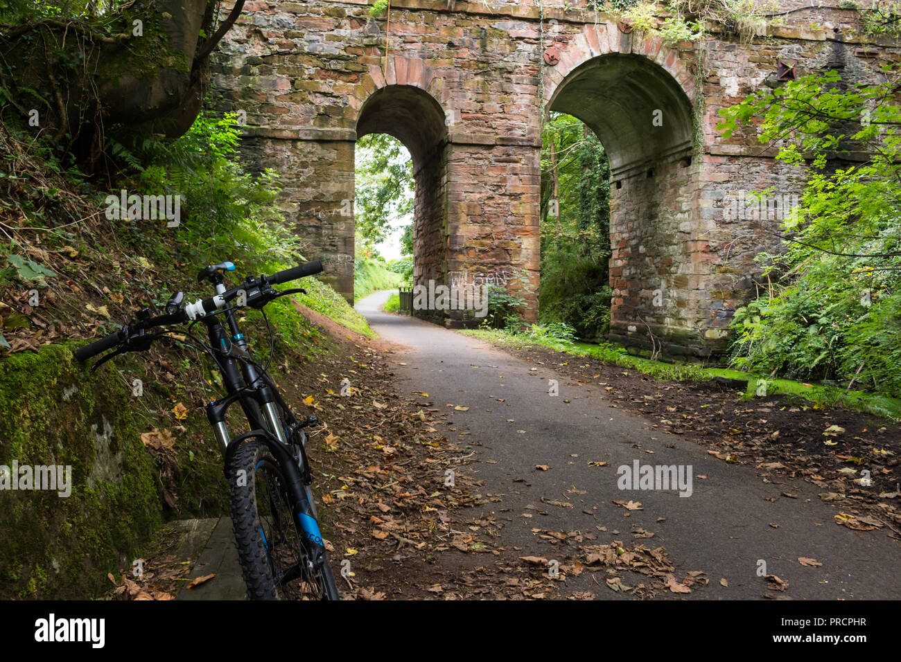 A bicycle parked on the Lagan towpath, between Lisburn and Belfast at a stone bridge whilst the cyclist takes a rest. - Stock Image