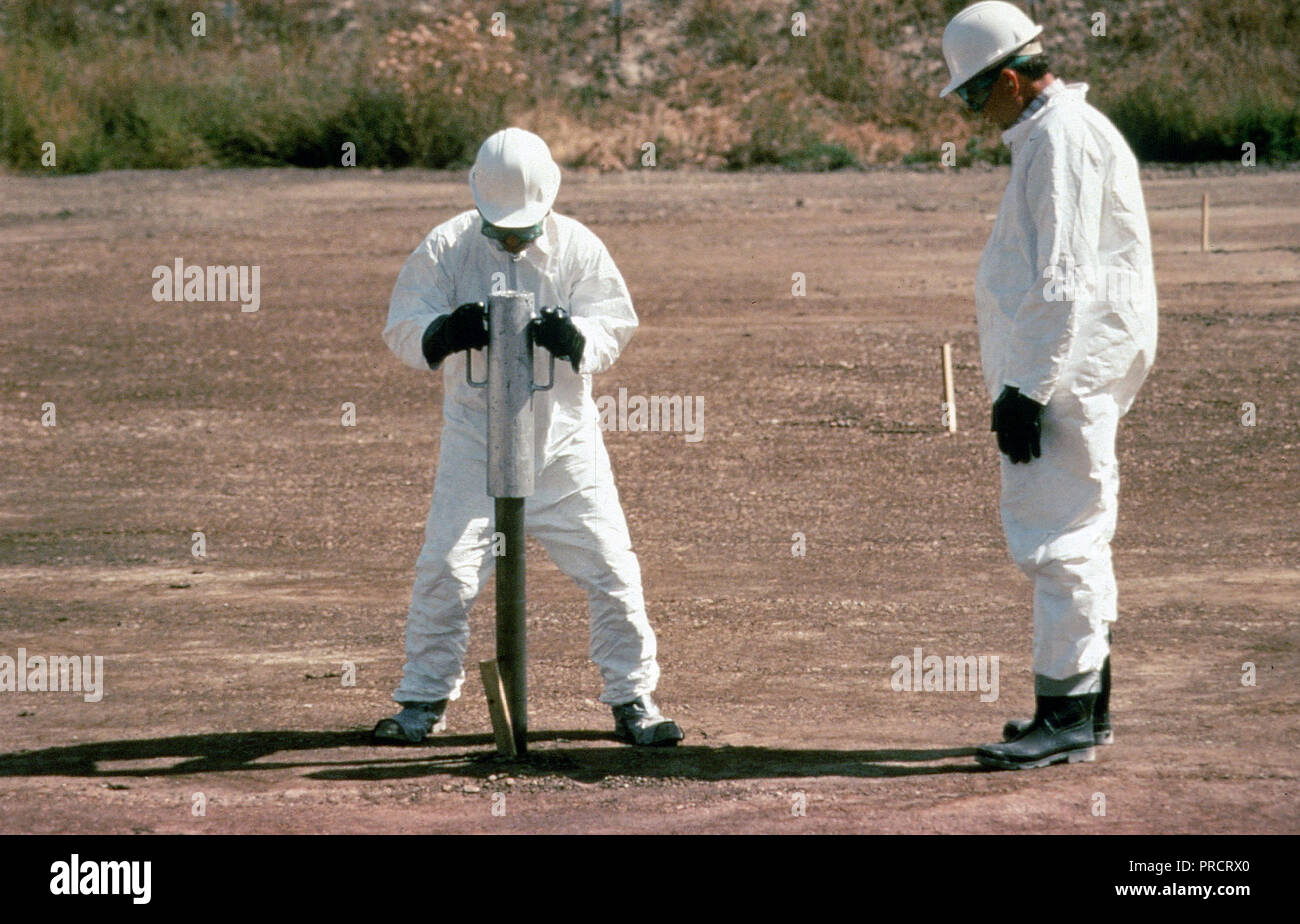 Scientists collecting a Giddings tube core sample from the land treatment unit - Stock Image
