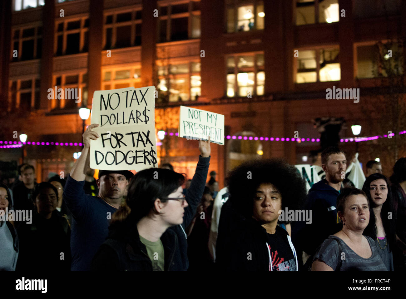 Protesters in Oakland carry signs reading 'no tax dollars for tax dodgers' and 'not my president' against the election of Donald Trump on Nov. 9, 2016 - Stock Image