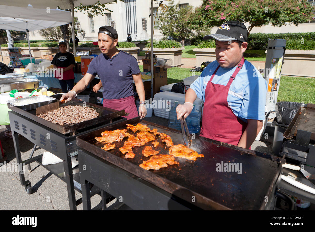 Hispanic cooks grilling meats at an outdoor festival - USA - Stock Image