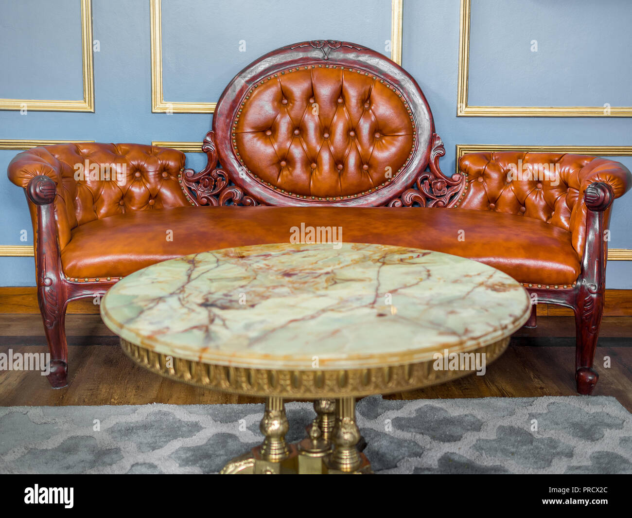 Picture of: Vintage Luxury Red Brown Leather Sofa With Marble And Brass Round Table On Gray Carpet And Wooden Floor On Light Blue And Golden Edge Wall Background Stock Photo Alamy