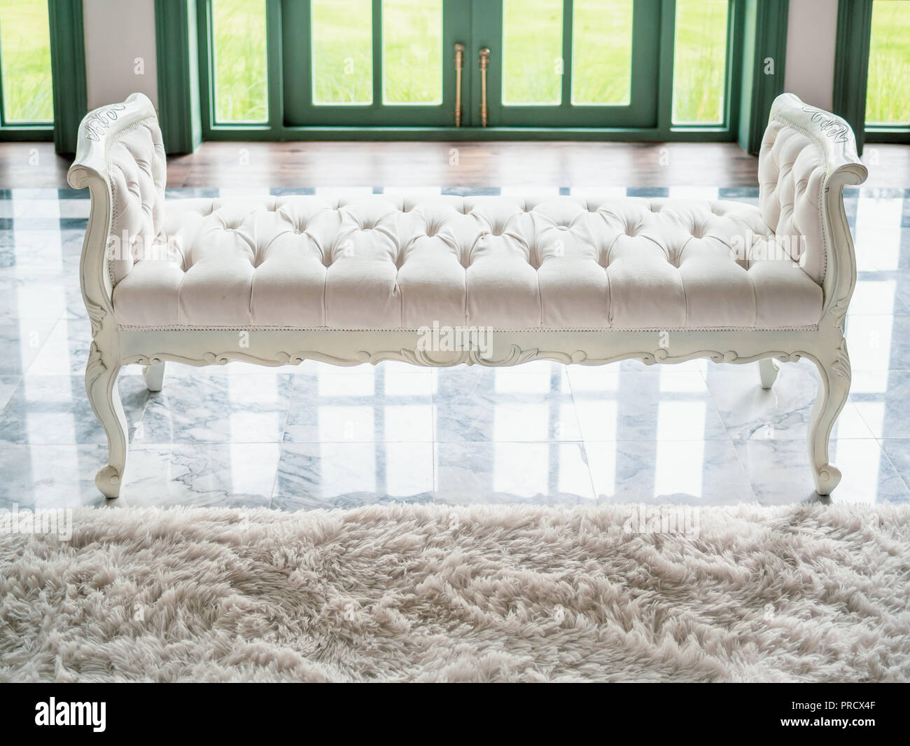 white tufted stock photos white tufted stock images alamy 13817 | classic vintage white tufted bench or bedroom bench on marble floor with white soft fur carpet in contemporary house near green door prcx4f