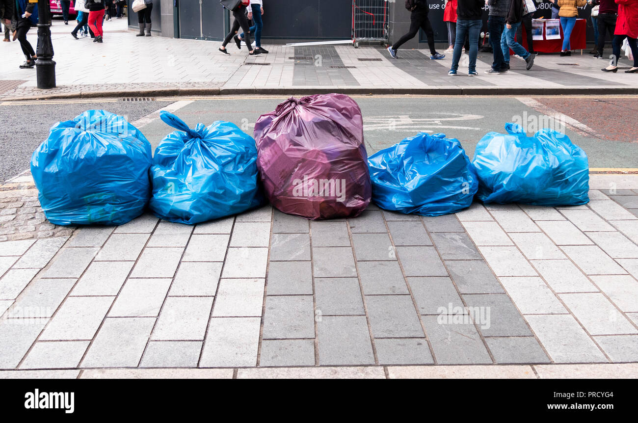 Waste bags left in street for collection. Unidentifiable people walking in the background - Stock Image