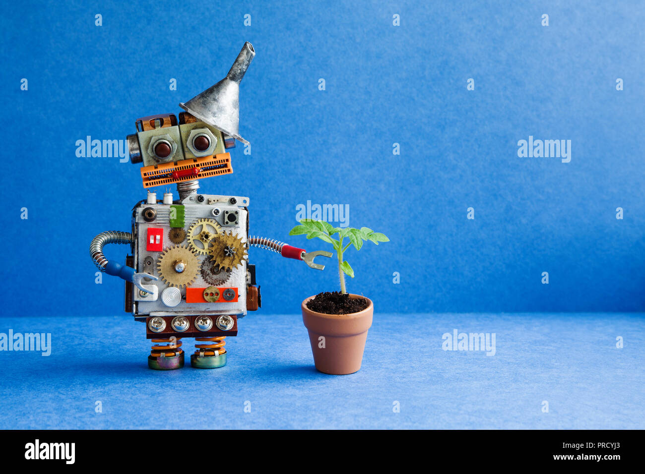 Comical robot with a small green sprout plant in a clay flower pot. Organic eco life concept. Blue background, copy space - Stock Image