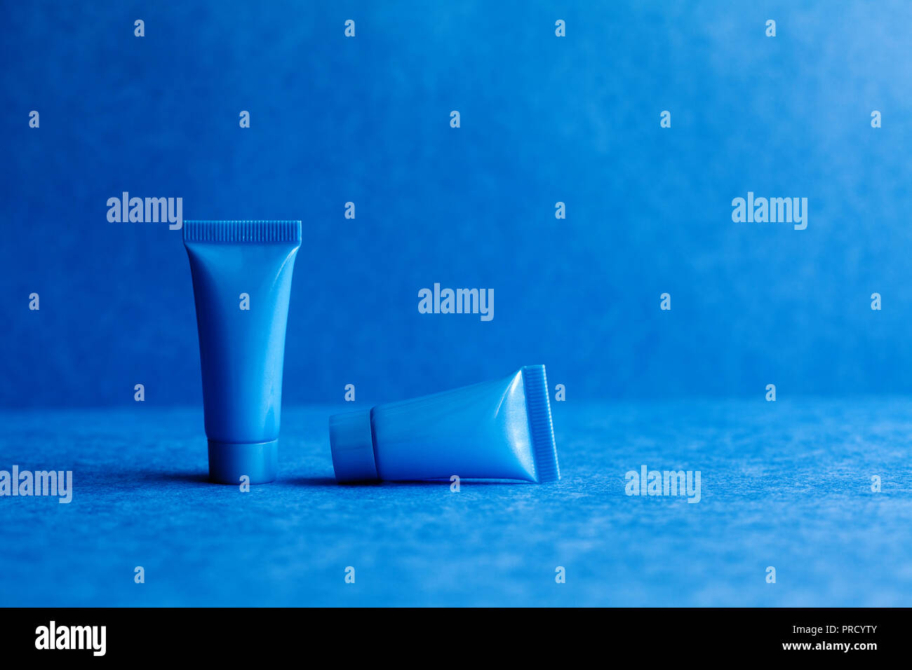 Blue cosmetic tubes on blue background. Blank opened plastic container, simple packaging design template. shallow depth of field, copy space photography. - Stock Image