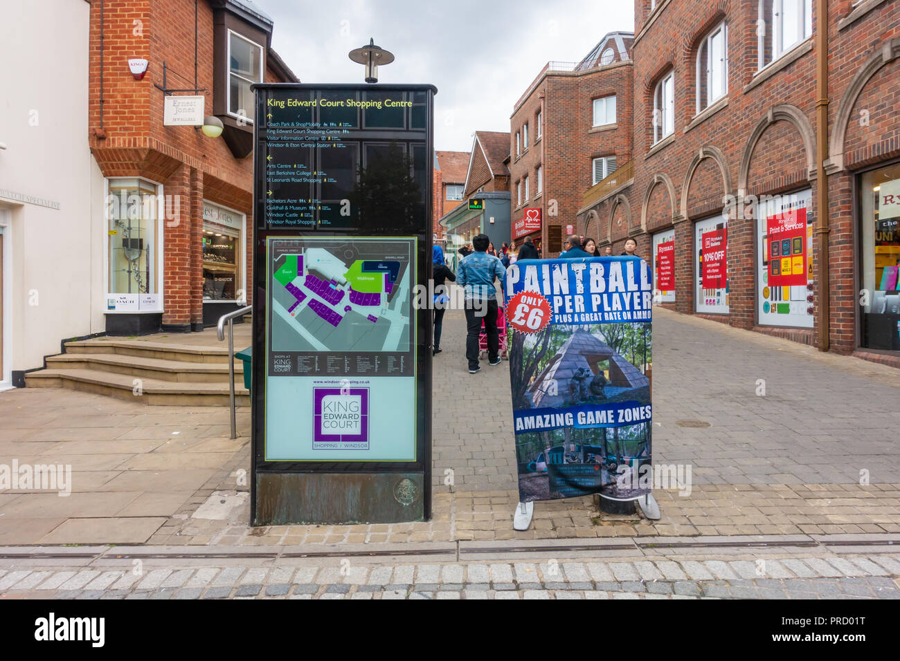 An information sigh for King Edward Court Shopping Centre on Peascod Street in Windsor, UK next to a sign advertising paint balling. - Stock Image