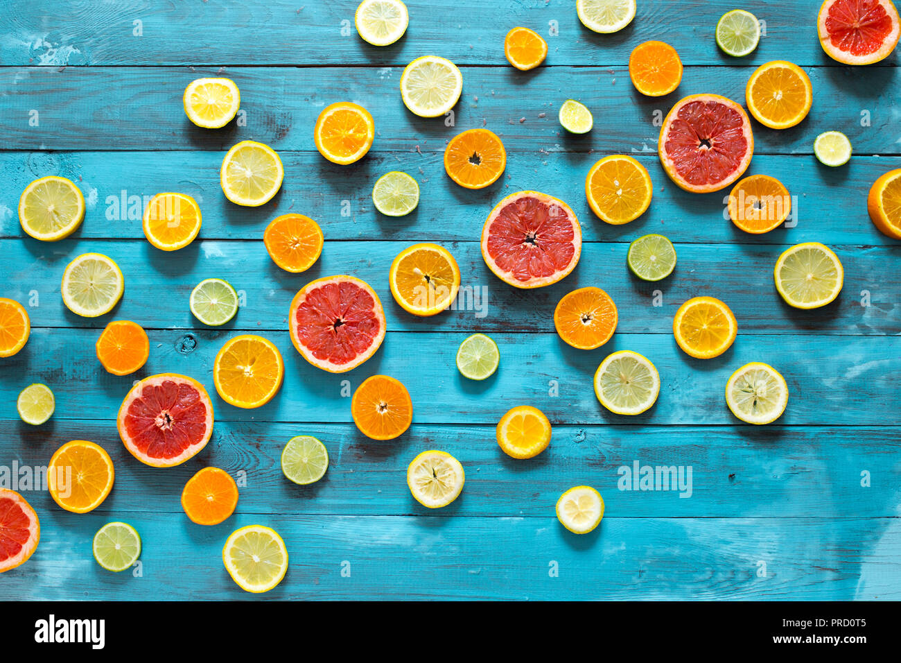 Fruit background. Colorful fresh fruits on blue wooden table. Flat lay - Stock Image