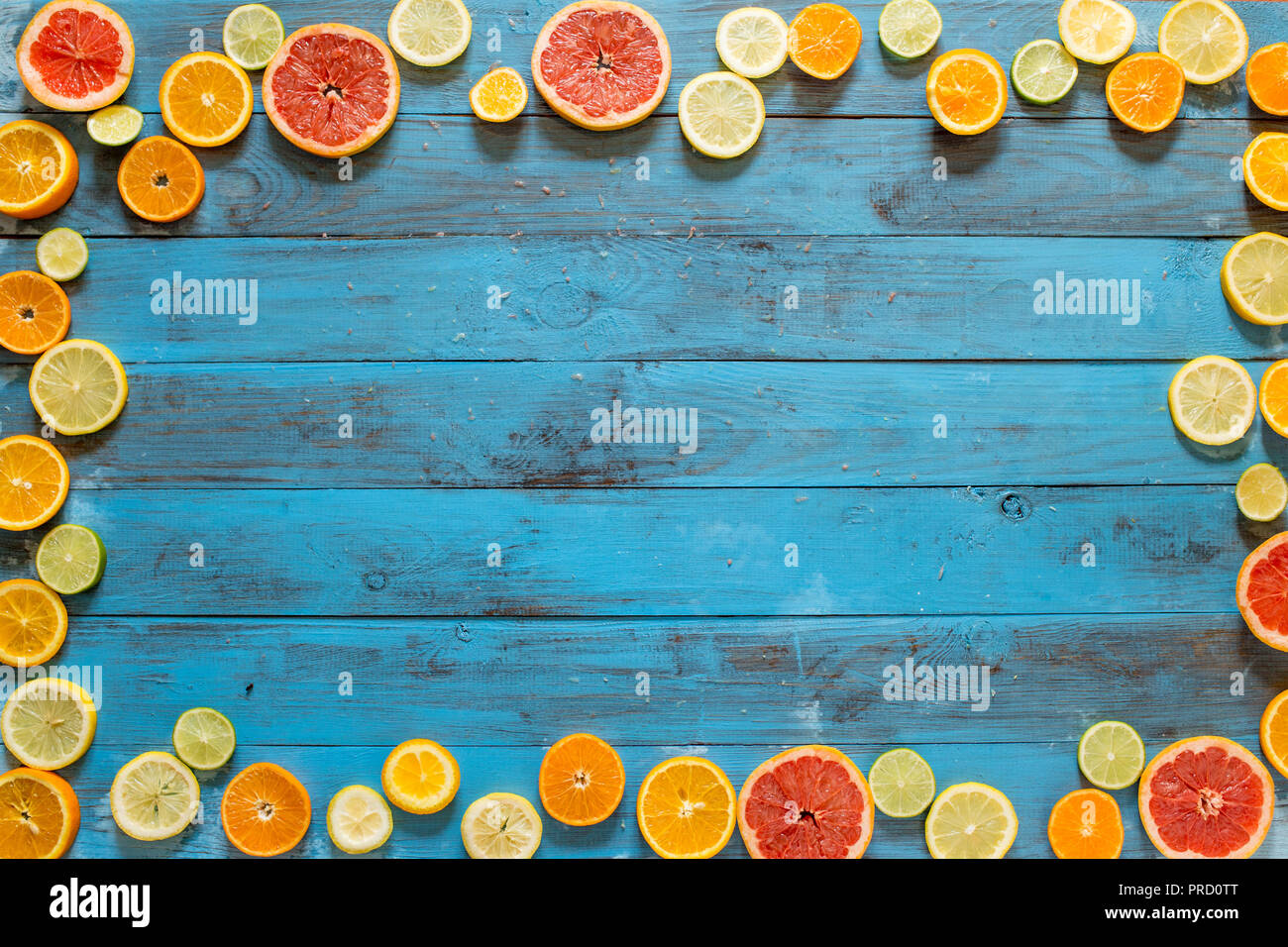 Frame made of citrus fruits slices on blue planks - Stock Image