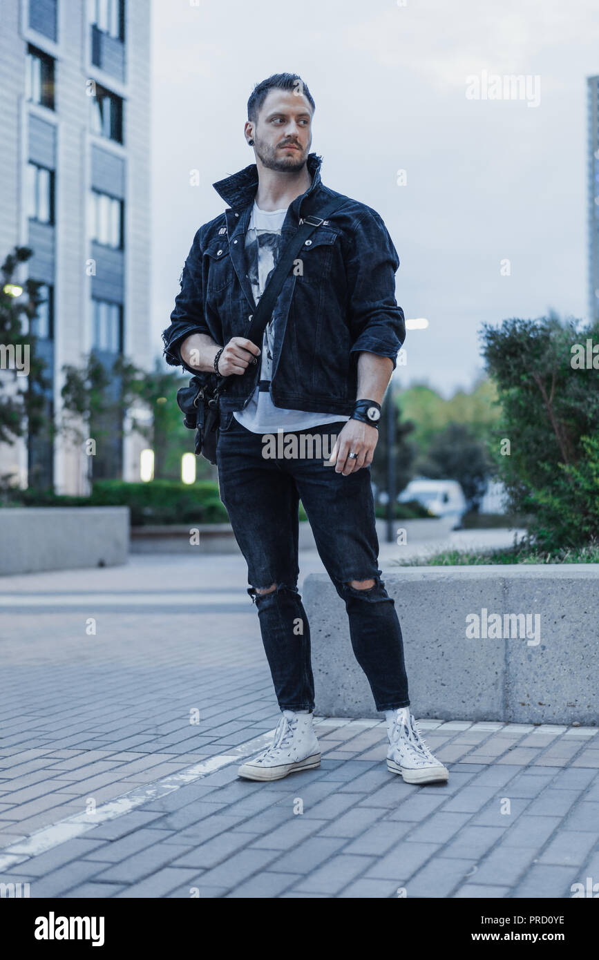 c2585beb Young attractive man in black jeans jacket standing on cityscape background.