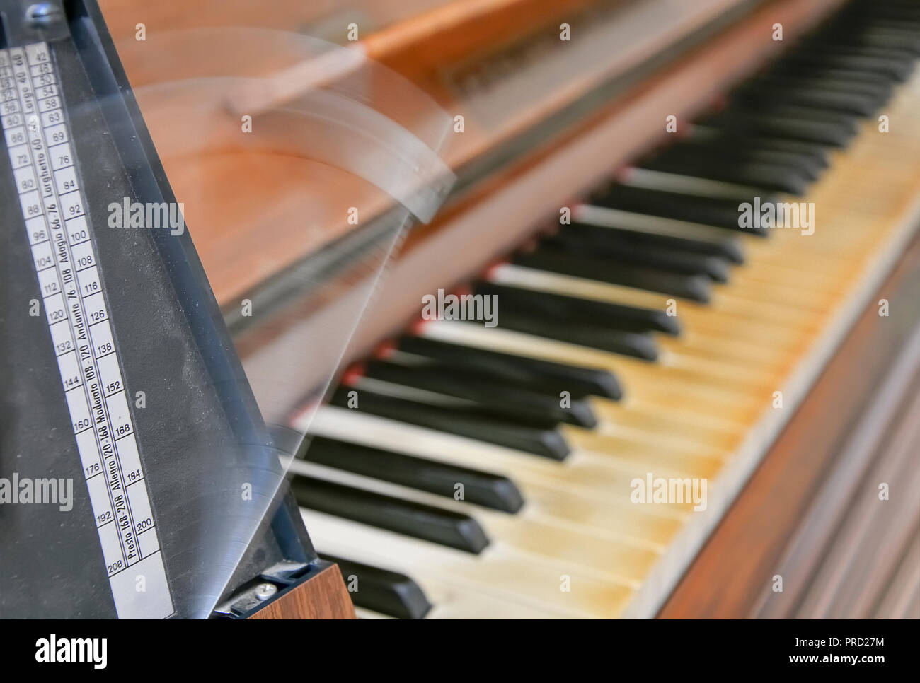 Antique metronome marks the rhythm of the music on an old wooden piano - Stock Image