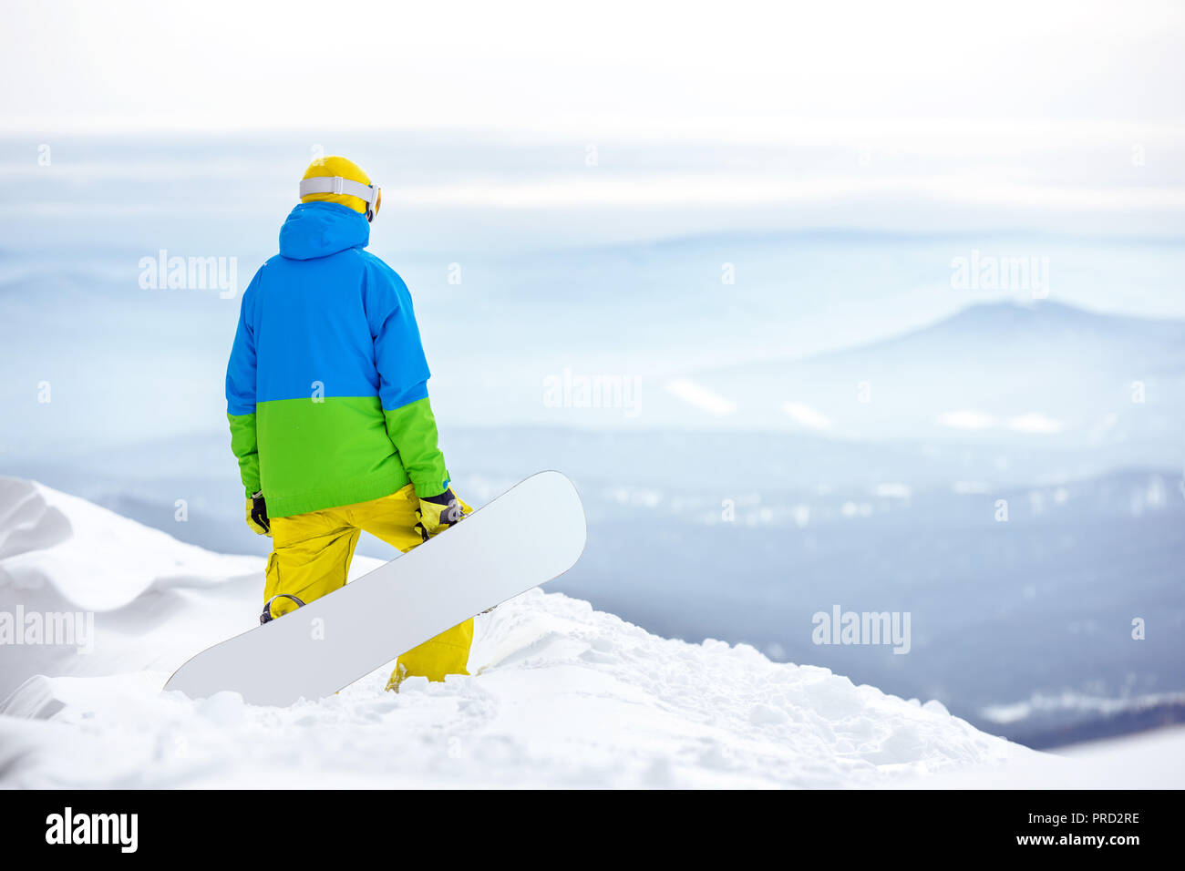 Snowboarder with snowboard stands on the top of mountain and looks to view - Stock Image
