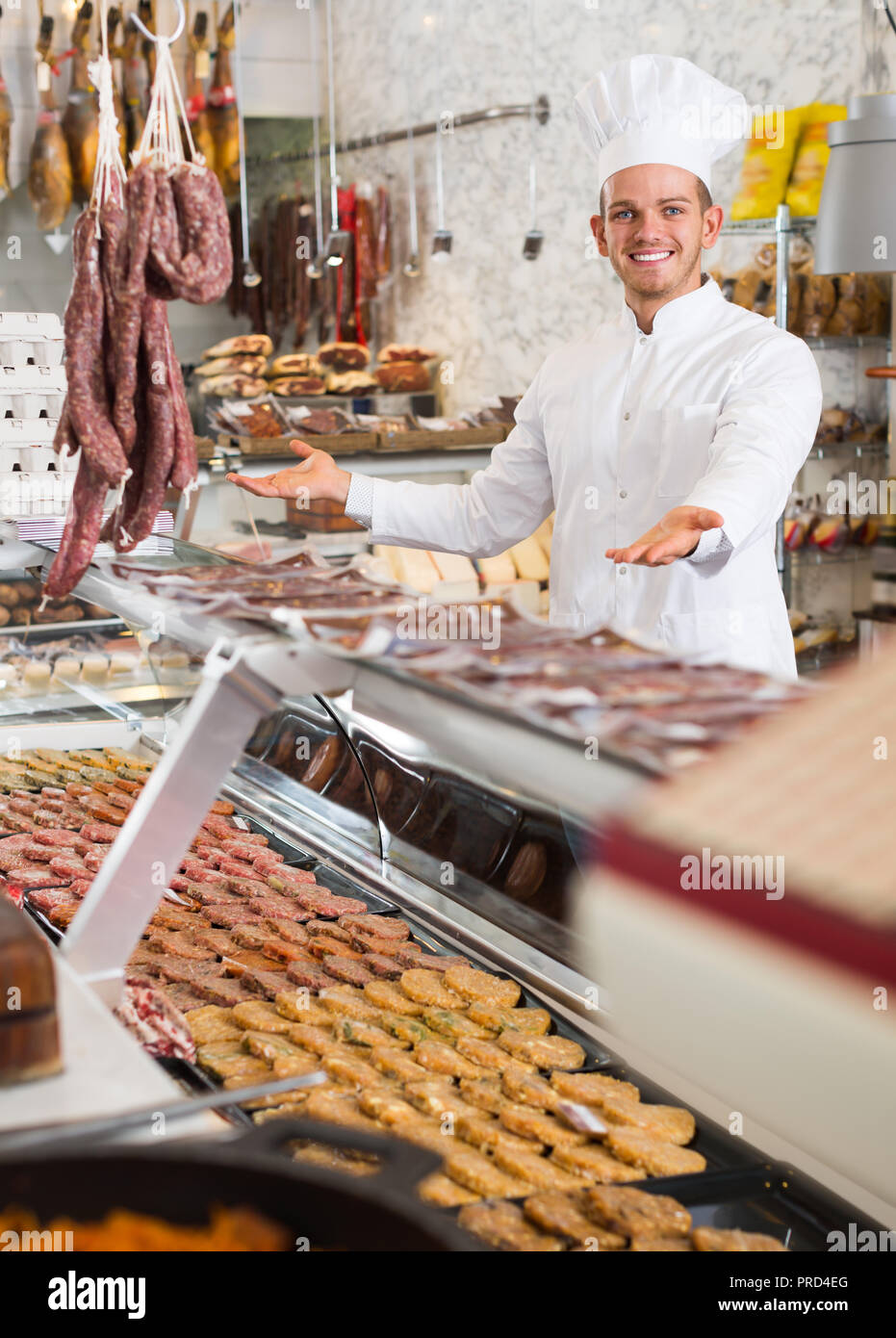 Glad ordinary male seller working at meat market - Stock Image