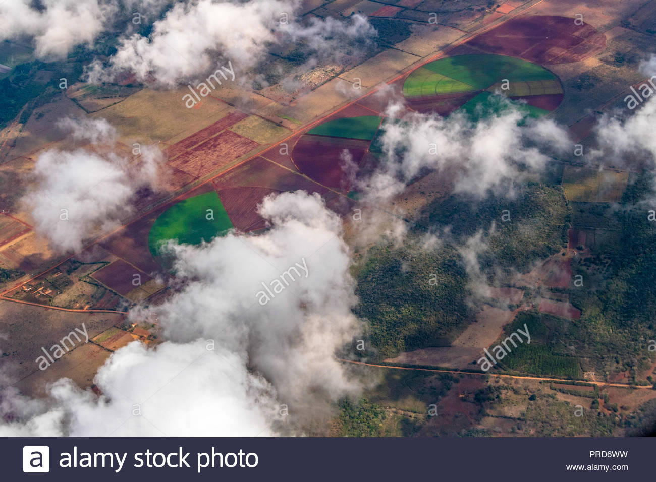 Clouds above the beautiful Cuban countryside. Tropical Caribbean climate or weather. Plane passenger point of view. - Stock Image