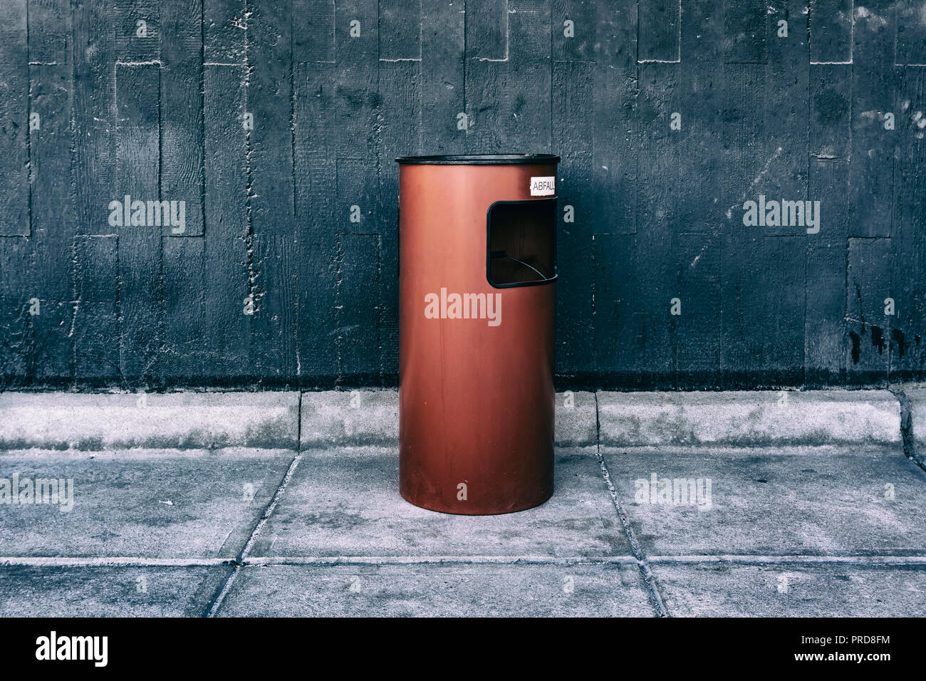 Berlin, Germany, September 30, 2018:  Close-Up of Ashtray on Red Garbage Can Against Gray Wall Stock Photo