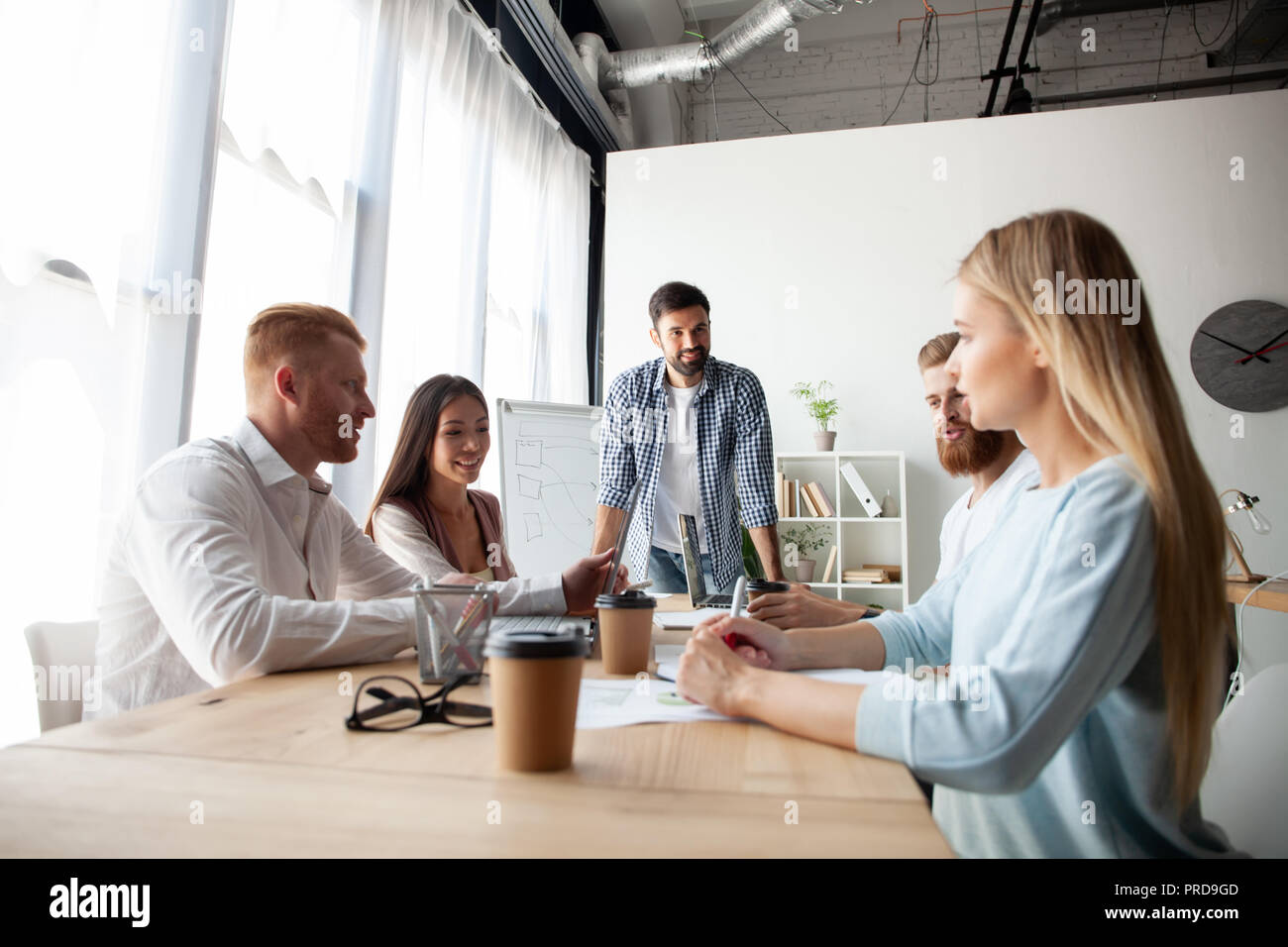 Young team of coworkers making great business discussion in modern coworking office.Teamwork people concept - Stock Image