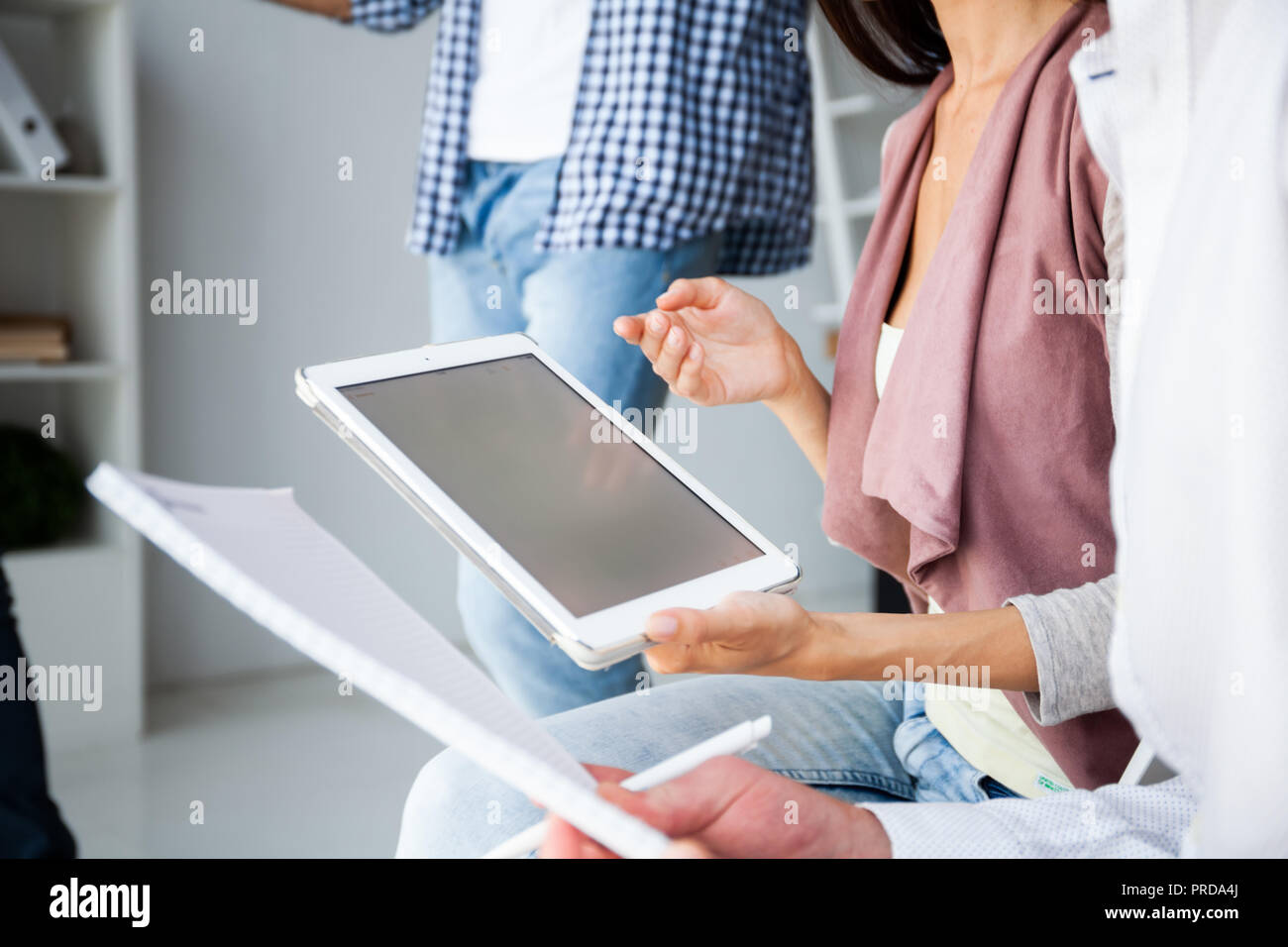 Business, office concept. Woman's hands using tablet with financial document - Stock Image