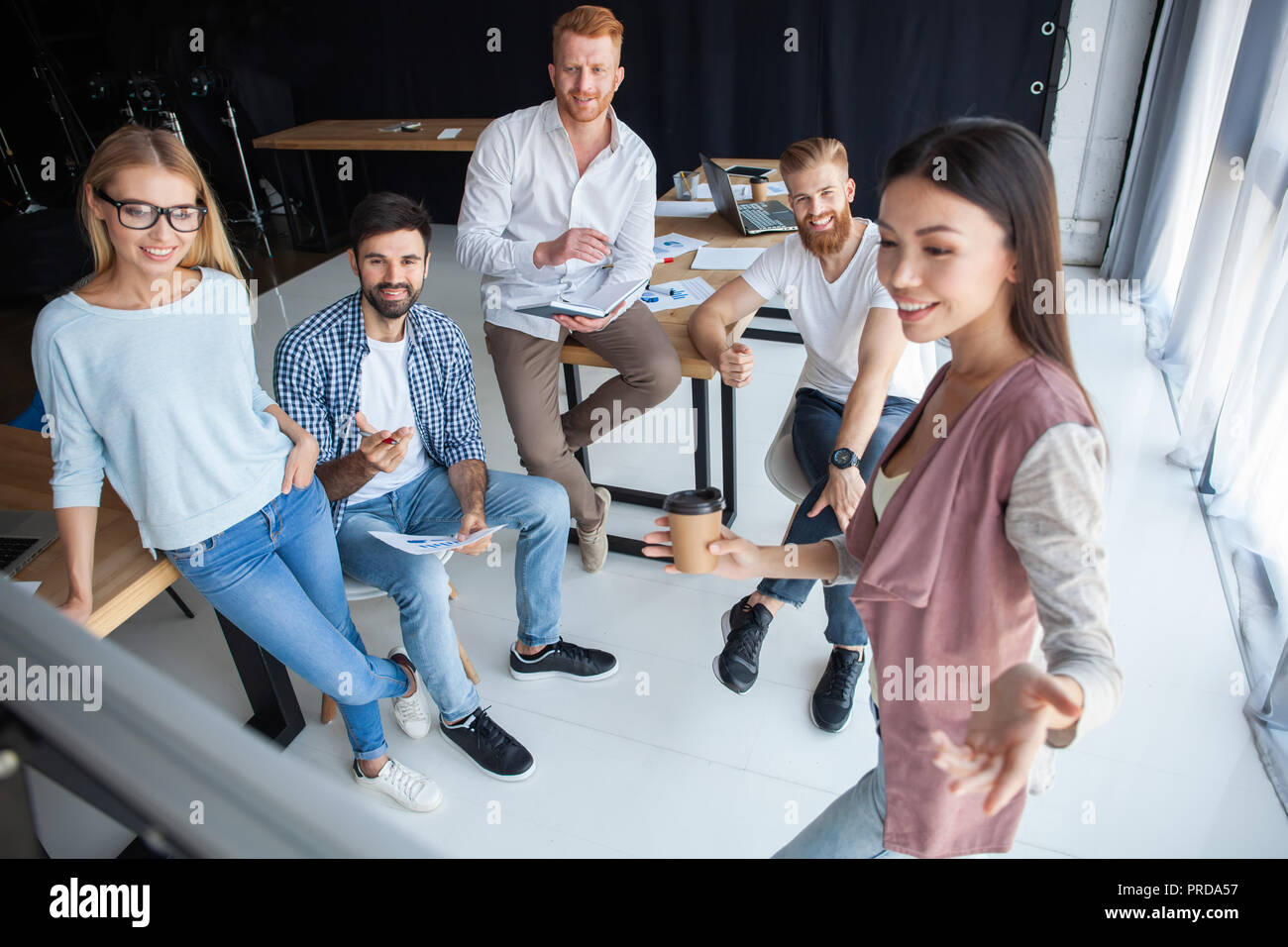 Group of young colleagues dressed casual standing together in modern office and brainstorming. - Stock Image