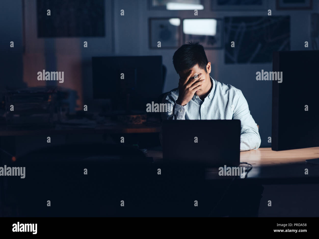 Exhausted Asian businessman working late at night in an office - Stock Image