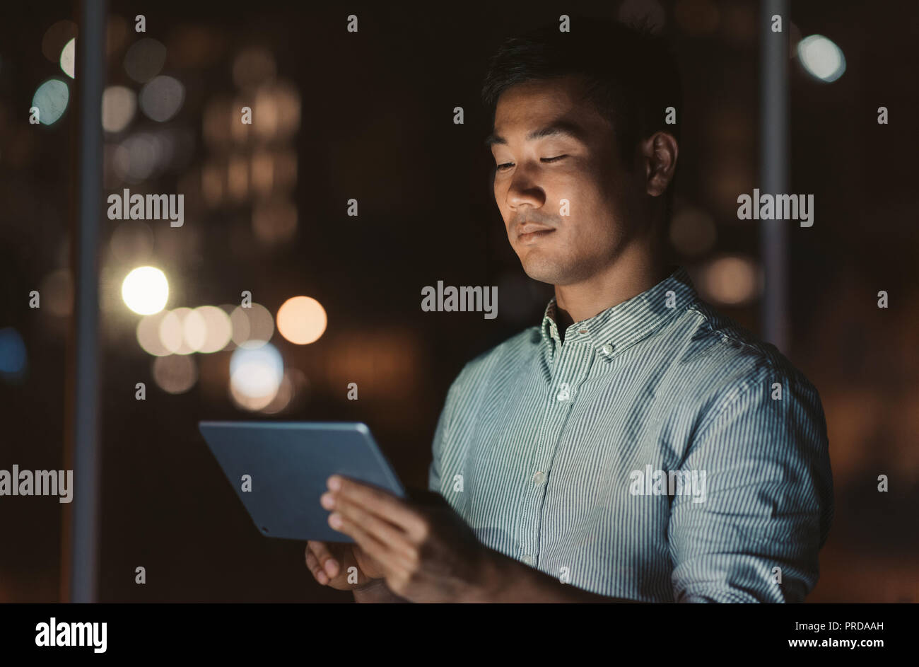 Asian businessman standing in an office at night working online Stock Photo