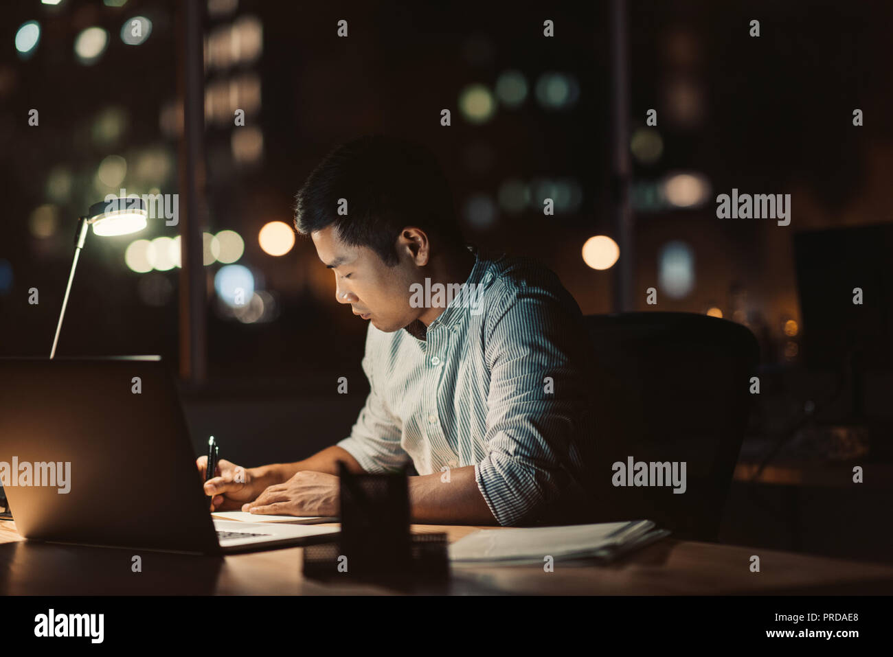 Asian businessman working at his desk late into the evening - Stock Image