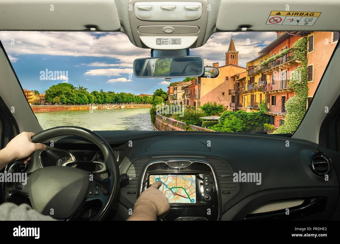 Driving a car while using the touch screen of a GPS navigation system in Verona, Italy - Stock Image